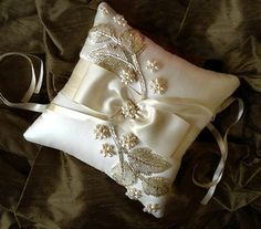 Gorgeous ivory silk dupioni ring bearer pillow with fanciful silver leaf glass bead appliques and genuine freshwater pearl sterling silver handwired flowers.The ribbon is supple double faced satin and it has a silk strap on the back for the ring bearer to hold. Measures about 8 inches square or about 20 centimeters and is tufted with a mother of pearl button on the back.