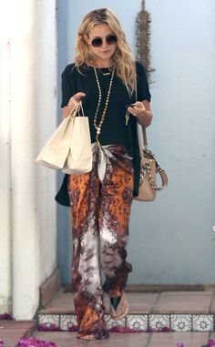 What's not to love about this boho-beautiful look? She styles colorful trousers, a long statement pendant and (of course) her Maison Martin Margiela bag.