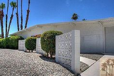 MCM privacy walls. Notice the front yard filled with rocks....no yard work! This home is probably in the California desert where it gets very hot in the summer. Lawns would require too much water.