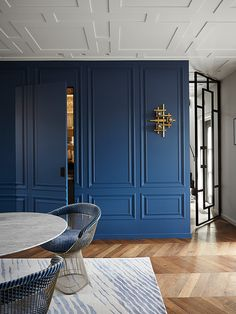 A traditional modern Amsterdam loft by Sascha Faase. The painted paneling on these walls disguise a hidden door. The blue is a stunning color that echos the patterns on the rug and the Knoll chairs. House Design, Room Design, Interior, Home, Modern Classic Interior, Ceiling Design, House Interior, Interior Design, Hidden Doors In Walls