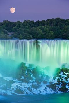 The American Falls with Full moon at dusk lit with lights photographed from Niagara Falls, Ontario, Canada - composite image