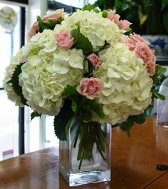 Low centerpiece of white hydrangeas, pink roses and pink spray roses in a vase with exposed stems.