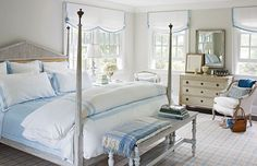 "Charming East Hampton Cottage - Traditional Home®  Patricia's love of Swedish style is on display in the couple's blue-and-white bedroom. An antique ivory-painted mirror and chest are set between new Marvin windows. Patricia prefers unmatched bedside tables, so one side is served by an antique wood table and the other has a table draped with embroidered ""Oakwell"" fabric from Cowtan & Tout."