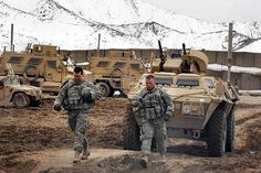 so Two U.S. Army soldiers walk their vehicle through the muddy paths