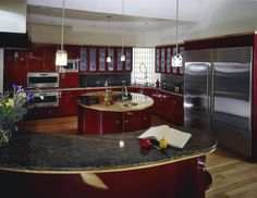 In a modern kitchen flush with bold red cabinetry, an innovative circular island holds the center. Wrapped in the same cherry red tone as the rest of the kitchen, the island sports a unique countertop, pairing granite with light wood. A set of dual sinks and wraparound cabinetry provide a surprising amount of utility in a small package.