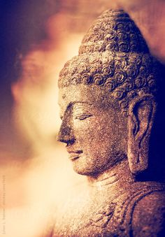 Stone statue of a buddha in meditation.Note: Fine grain added in postproduction. Retro-styled image.