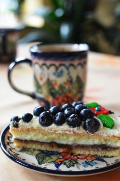 Sponge cake with plum jam, pudding, cream and blueberries