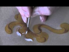 Great video by Gerhardt Mounet Lipp on how to paint Baroque scrolls. Notice how he (mostly) holds the paint brush perpendicular to the surface; this gives you more control over your strokes and enables you to finish with a fine stroke rather than a flattened, thick stroke that results when the brush is at an angle.