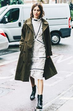 Alexa Chung wearing a khaki trench coat with a white lace dress and black boots.