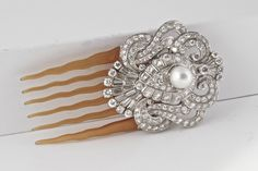 This is easily one of the most gorgeous hair pins I have ever seen. It is Art Deco with over 12 carats of incredible diamonds. The pearl in the center is a beautiful South Sea Cultured pearl and it is a beauty; creamy white with hints of pink. The comb is tortoise shell. There are no cracks in the comb. A few light scratches only that are almost not worth mentioning. This is a true work of art from one of the most exciting eras in jewelry design.