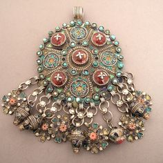 """Silver, coral, turquoises, enamel, resin, Algeria    Kabyles women receive their jewels from their parents the day of their marriage and they belong to their dowry: these enamelled silver fibules are named """"ibzimen"""". Blacksmiths of north of Algeria are specialized in this art : they embellish it with green, yellow and blue enamel."""