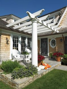 "The ends of the pergola beams are held off of the roof with custom stainless steel ""T"" shaped clips (similar to roof snow guards), that are fastened and flashed to the roof. The top end of each clip was mortised into the beam, plugged, sanded and painted. The beam end is held off and spaced approx. ½"" above the finished red cedar shingle. This gives the effect that the beam looks as if it is penetrating through."