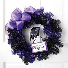 A+purchased+tinsel+wreath+is+only+part+of+the+door+display+in+this+eerie+idea.+Adhere+fake+purple+nails+to+a+jewelry-display+hand+form+(found+at+hobby+stores),+and+mount+it+in+the+center+of+your+wreath.+The+hanging+sign,+available+below,+makes+a+creepy+note+to+hang+from+outstretched+fingers.