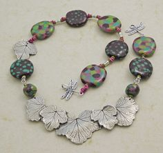 Inspiration of the Day - Currants for Kermit - Kazuri & Dorabeth Necklace     Henna, Peacock, Apple Green & Rose Pink are just some of the new Kazuri Colors we have added this winter.  The Dorabeth Designs Pewter Current Leaf focal & Dragon Fly Toggle add to the whimsical theme of this design created by Jamie Hogsett.    Click below to see all the components that make up this necklace:  http://www.antelopebeads.com/Currants-for-Kermit-Kazuri-Necklace/View-all-products.html