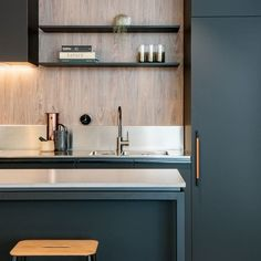 Steel/powder coated leg and shadow line to island. Also shows modern freestanding range hood. Splash back in same material as bench, then tiles/timber whatever above on large wall.