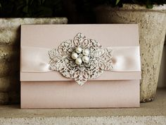 Invitation 1015: Blush Pearl, Cream Smooth, Pinyon Script, High Tower, Blush Ribbon, Brooch/Buckle T, Metal Filigree F6 - Silver
