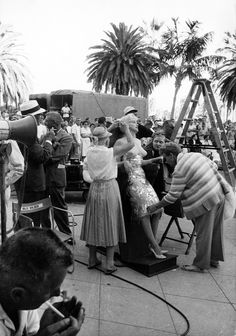 Marilyn Monroe rests on a leaning board during production of SOME LIKE IT HOT, 1959. Dialog coach Paula Strasberg is to the immediate right of Monroe. Others unidentified.