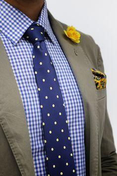 gray jacket. blue gingham shirt. blue tie. yellow pocket square + lapel pin.