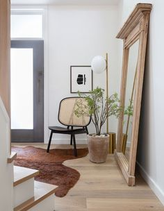 Designer Nyla Free knows how to make an entrance! A vintage mirror, curved cane chair and rich brown rug are a lesson in layering in her foyer. | Photographer: Phil Crozier Loft Kitchen, Farmhouse Style Kitchen, Vestibule, Yellow Sofa, Wood Bookshelves, Oak Panels, Best Paint Colors, Banquette, Ship Lap Walls
