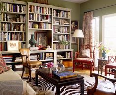 Busy but not too busy living room with zebra rug, red Chinoiserie chairs, and a great built in bookcase...love it as long as the zebra is faux!