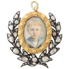A fabulous antique hand painted miniature of a young boy in a sailor's uniform. The miniature is surrounded by gilt silver and gold, set with rose cut diamonds. DESIGNER: Not Signed MATERIAL: Gold, Gi