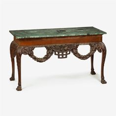 Pair of Irish George II style carved mahogany marble top console tables, one probably early 19th century, the other later - The rectangular verde antico marble top over cavetto edge and plain frieze, the apron carved to show a pierced floral basket flanked by oak leaf and acorn swags, the sides centered by shell carving, raised on cabriole legs with acanthus carved knees, terminating in hairy paw feet. (2).    H: 39 1/4, W: 54, D: 26 in.