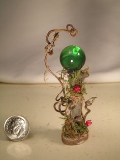 This Gazing Ball is done in mostly natural materials. Each twirled piece, floral accent, and moss bits were hand selected and carefully placed to make