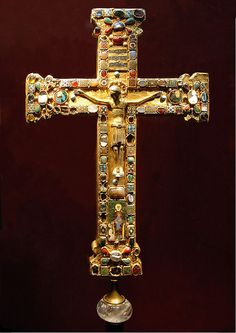 """""""Mathilda Cross"""" made for Mathilda, Abbess of Essen, 973–1011, with the body of Christ being a slightly later replacement. Mathilda is shown kneeling before the Virgin and Child in the enamel plaque. Probably from Cologne or Essen, the cross demonstrates the use of several medieval technologies such as figurative sculpture, casting, filigree, enamelling, gem polishing and setting, and the reuse of Classical cameos and engraved stones."""