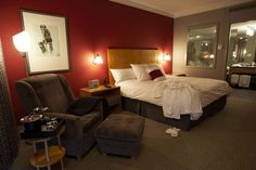 red accent wall with white bedding and brown to break and balance - perhaps nice black/white illustrations on the wall?