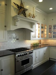 kitchens - white glass-front shaker kitchen cabinets honed black granite tops pot filler subway tiles backsplash Floor to ceiling white glass-front