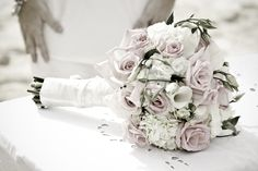 Photo of a brides bouquet, which is sitting on a table on the sand in The Bahamas. This photo was taken by Stop Motion Productions, a Bahamas Wedding Photographer.