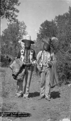 Fred and Clarence Old Horn. The young brothers are both wearing what was, at the time, considered a contemporary Apsáalooke men's outfit. Each is wearing a reservation style hat wrapped in a scarf, a fully beaded vest with Crow floral designs, gauntlets beaded with Crow floral design, multilayered necklaces, buckskin pants, and moccasins. William Wildschut photograph collection. Date: 1917-1928. NMAI Archive Center, Smithsonian Institution.