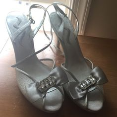 """Silver peep-toe party shoe Silver peep-toe shoe with bow detail.  Center of bow has rhinestones.  Super sexy ankle strap.  4"""" heel.  Classy pair of shoes.  Worn once. Nina Ricci Shoes"""