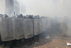 Ukrainian police officers take cover behind shields during clashes with demonstrators, who are against a constitutional amendment on decentralization, outside the parliament building in Kiev, Ukraine, August 31, 2015. Approval of legislation for special status for parts of Donetsk and Luhansk regions, which are largely controlled by Russian-backed separatists, is a key element of a peace agreement reached in Minsk, Belarus, in February. REUTERS/Valentyn Ogirenko