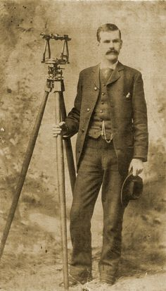 surveyor posing with his equiptment in a photographers studio
