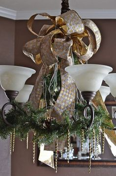 gold and silver ribbon, evergreen branches with pinecones to cover a chandelier