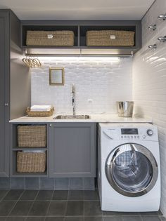 This laundry room with gray cabinets, white subway tiles and brass hangers looks fresh and modern