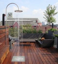 """This rooftop deck with outdoor shower is made of ipe, also called Brazilian walnut, which  Bob Vila calls """"an extremely dense material and also a renewable product—one of the best choices for outdoor decking."""""""