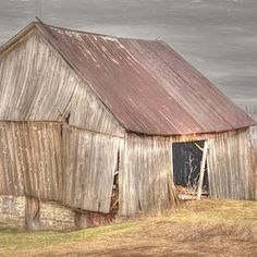 WEATHERED RUSTIC BARN IMAGE This weathered barn picture shows a rustic barn with stormy skies The barn has seen better days, yet it still holds beauty. Can you imagine the farmers working here? Click to see options and other barn photography prints. #barnphotography #weatheredbarn #rusticbarn #farmhousedecor #barnpictures