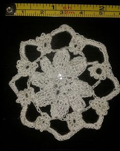 Tiny flowers around a larger flower - Pattern in: The Go-to Book for Irish Crochet Motifs http://www.amazon.co.uk/gp/product/1596359234