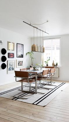 Mid-century styled dining room with sleek metal frame leather dining chairs, an eclectic gallery wall and line of metallic gold and white pendant lights.