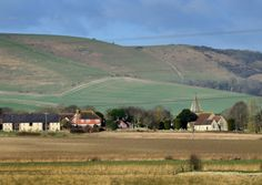 View of the village and church spire from Southease with the South Downs in the background.