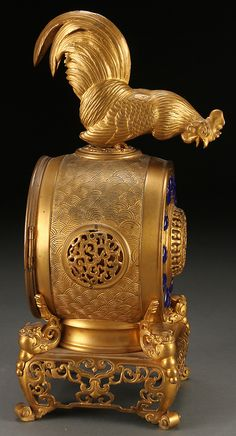 AN INTERESTING CONTINENTAL GILT BRONZE CLOCK FOR THE CHINESE MARKET, 19TH CENTURY.  The circular movement embossed with stylized wave pattern raised on a reticulated base with mythical beast support and with chapter ring enameled with Chinese characters surmounted with a figural rooster.