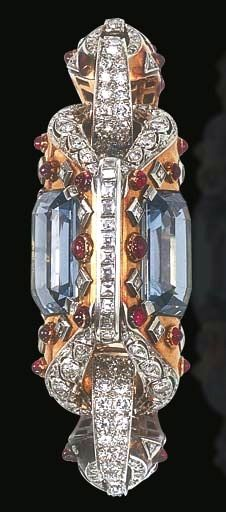 A RETRO AQUAMARINE, RUBY AND DIAMOND BRACELET Of hinged design, centering upon a polished gold sculpted geometric openwork motif, set with two rectangular-cut aquamarines, decorated with cabochon ruby and square-cut diamonds, enhanced by old European and square-cut diamond trim, joined by old European and single-cut diamond arched links, to the tapering polished gold bracelet and clasp of similar design, mounted in gold, circa 1950, 2 1/8 ins. diameter