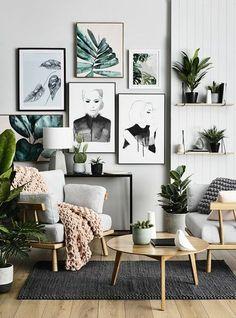 mur de cadres, parquet stratifié, plaid en crochet, lampe blanche, fauteuil blanc en bois, plantes vertes