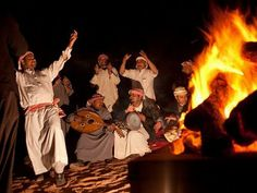 The wonders of Saudi Arabia: Bedouins men singing and playing instruments around a campfire