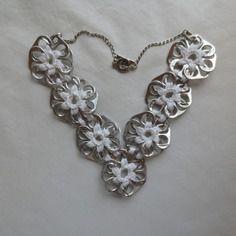 Collier blanc en capsules de canettes argentées recyclées crochetées une à une en forme de fleur.