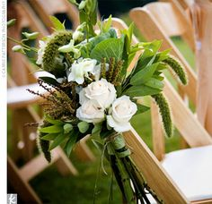 Organic-style baskets of cream garden roses, mini cymbidium orchids, millet, and fresh bay were tied to the aisle chairs with cream and brown satin ribbon.