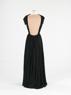 The front of the gown is reminiscent of a chiton, which was worn gathered and pinned at the shoulders and girdled at the waist. Here, however, the gathers are pleats that extend over the shoulders and frame a large cutout in the back.