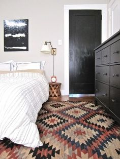 Classic Rug used in a bedroom with clean lines.  rug/white bedding  black wood accents #bedroomrug